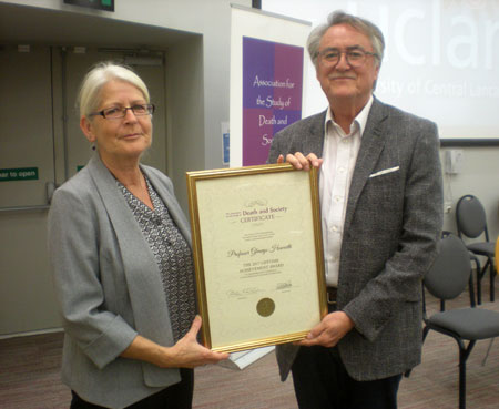 Professor Glennys Howarth is presented with a framed certificate  by Professor Allan Kellehear